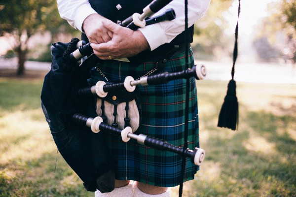 A set of bagpipes held near a kilt.