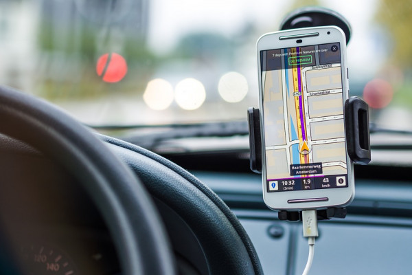 A smartphone mounted on the car dashboard assisting with navigation