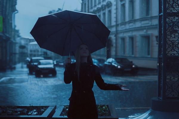 A girl holding an umbrella checks if it is still raining