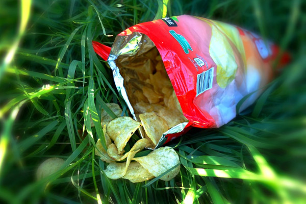An open packet of crisps on grass