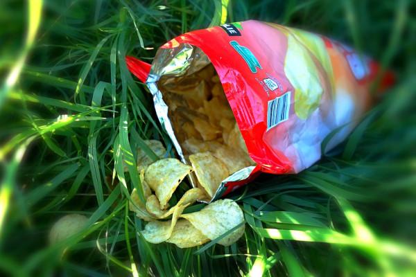 An open packet of crisps on grass