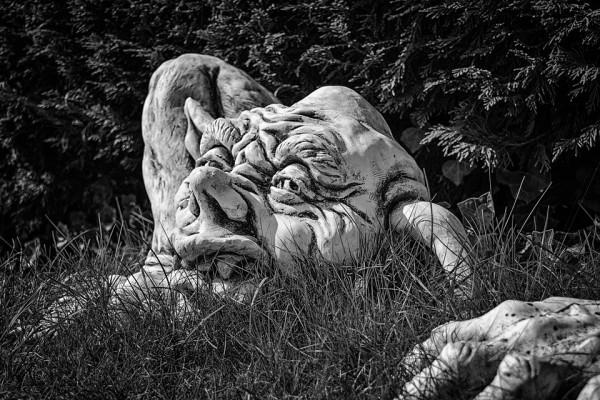 A statue of a trolls head in grass