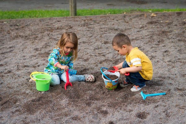 Two young children playing in the sand.