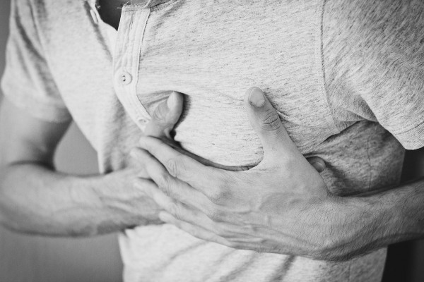 Someone pressing their hands to their chest, around their heart.
