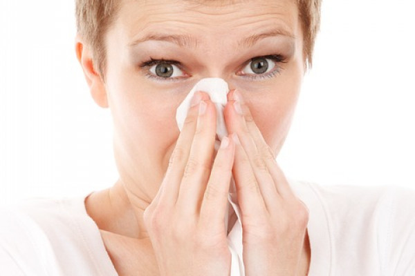 Woman holding a tissue to her nose.