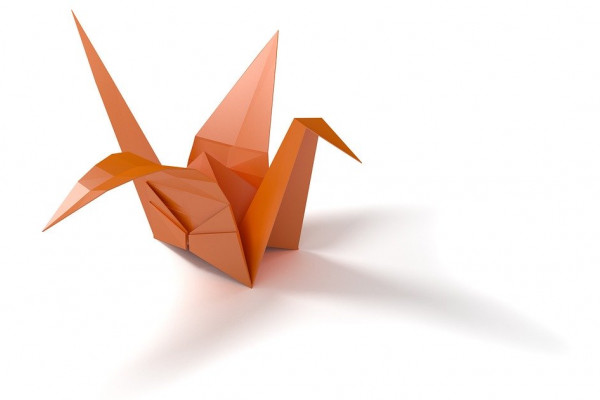 A traditional Japanese origami crane folded with orange paper