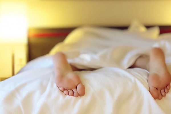 Feet of a sleeping person in bed