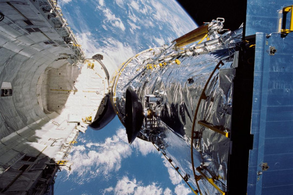 The Hubble Space Telescope is suspended above shuttle Discovery's cargo bay some 332 nautical miles above Earth