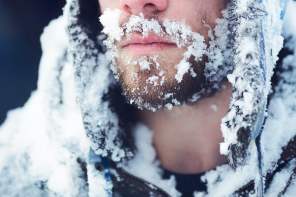 A bearded man with a winter coat covered in ice.