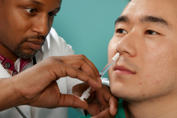 A doctor administering a vaccine up a patient's nose.