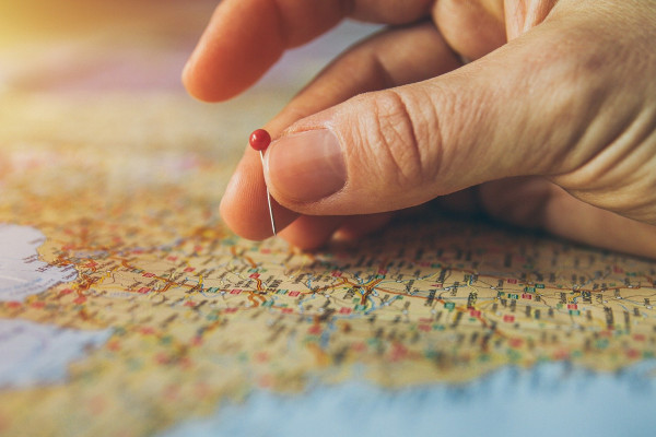 Person sticking a pin into a roadmap