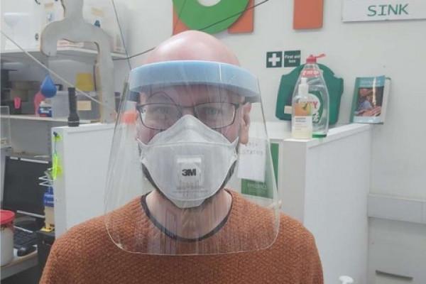 A Makespace volunteer wearing a plastic face visor.