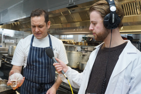 Chef Tristan Welch holding a haggis while Phil Sansom holds a microphone to his mouth