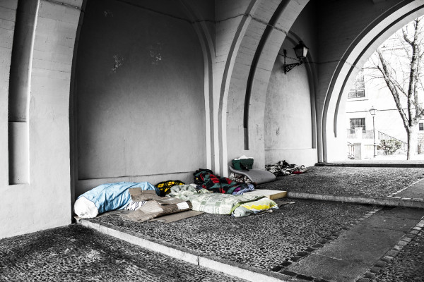 Beds of homeless people under an archway