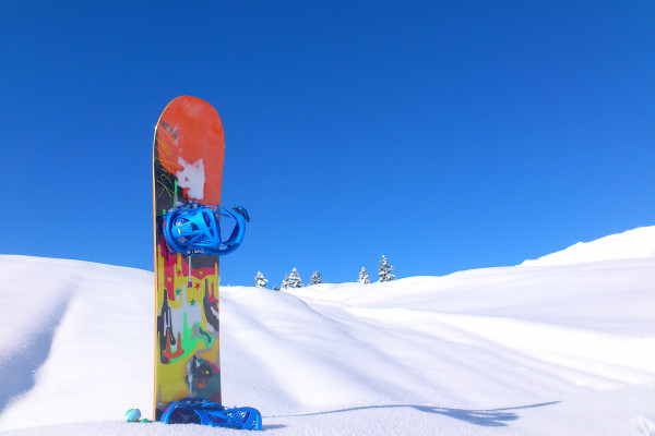 A snowboard stuck halfway into some snow.
