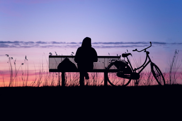 A woman sitting on a park bench watching the sunset