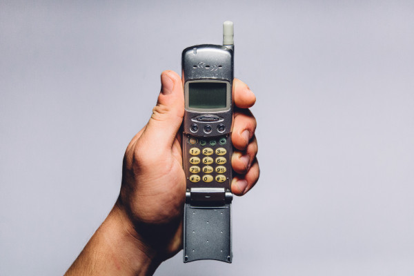 Image of a hand holding an old mobile phone