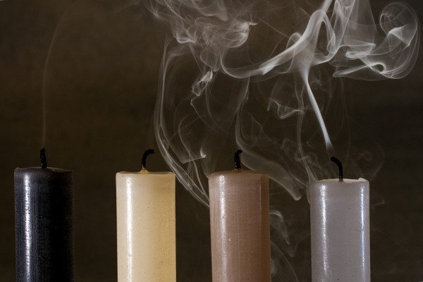 The image shows smoke rising from a candle.