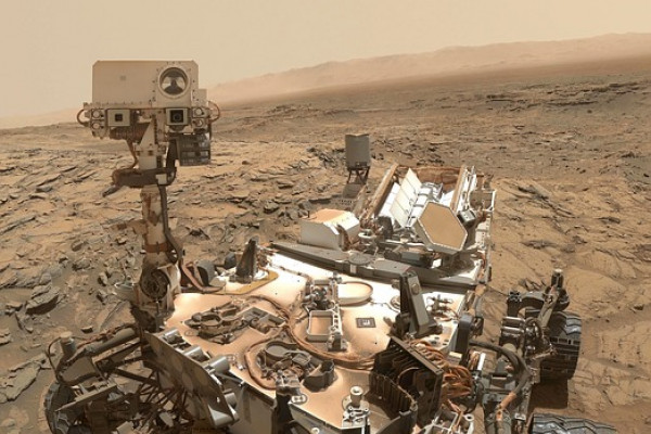 The image shows a robotic rover on the surface of Mars.