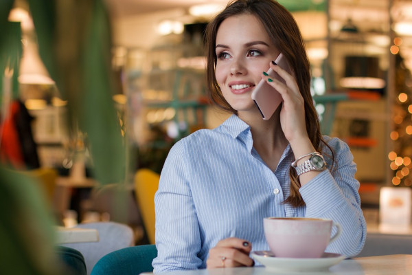 Woman speaking on a mobile phone over coffee