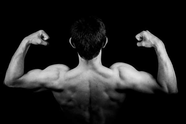 The picture shows a man flexing his back and shoulder muscles.