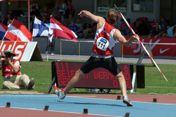 A man in a red vest pulling his arm back, ready to throw a javelin