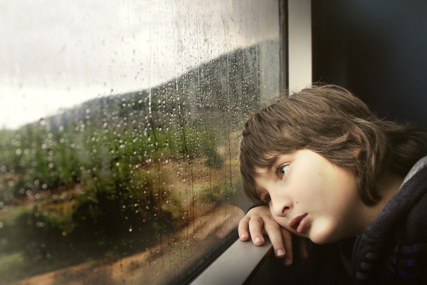 CHILD LEANING ON THE WINDOWSILL LOOKING BORED