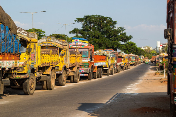 A line of trucks along a road in India.