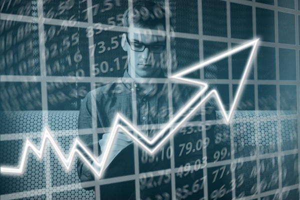 Financial imagery - a young man with glasses behind a rising graph.