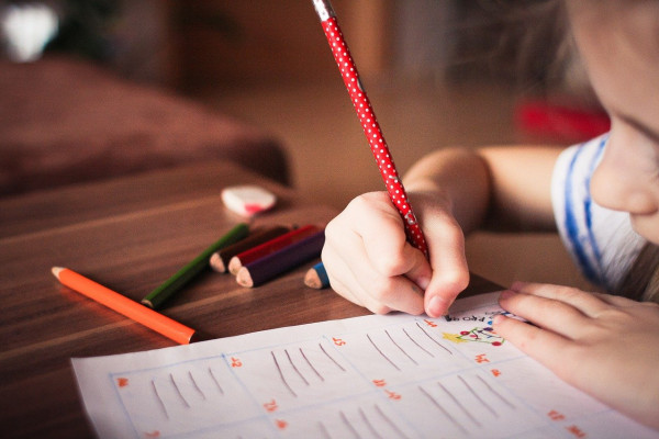 A young girl writing with a pencil.