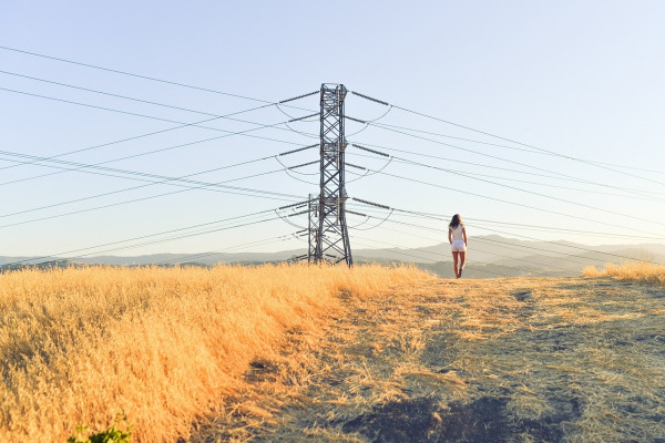 An electric pylon sitting in the middle of a field