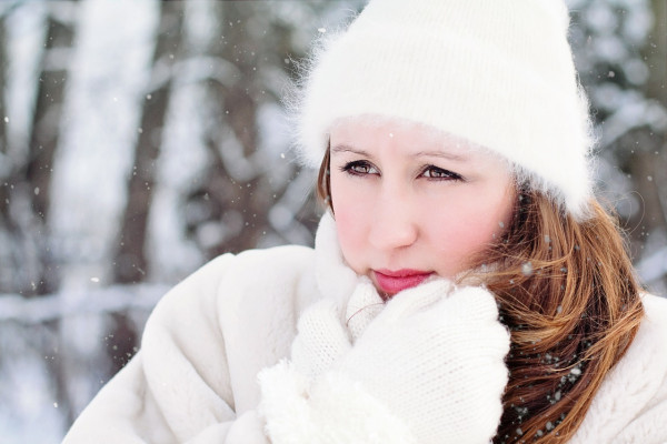A woman wrapped up warmly in a snowy forest.