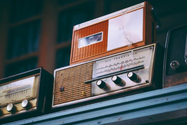 Some vintage radios sitting on a shelf