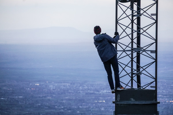 A man hangs from a 5G mast