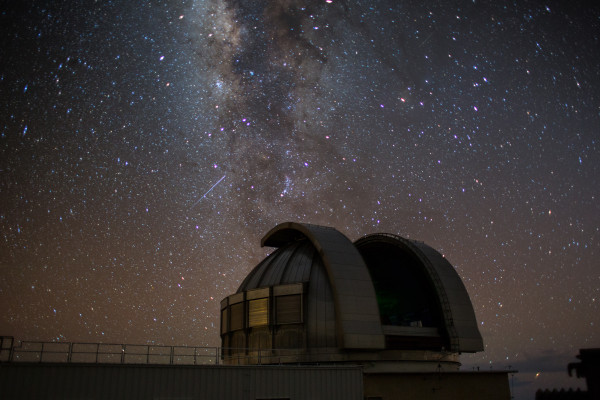 A large astronomical telescope against a dark starry sky.