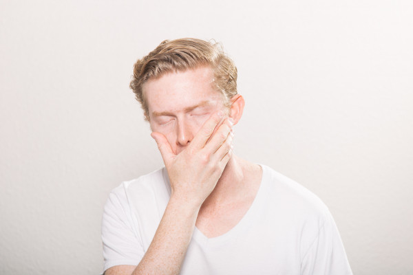 A tired man covering a yawn with his hand.