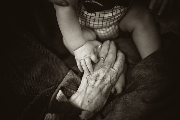 Young and old hands touching