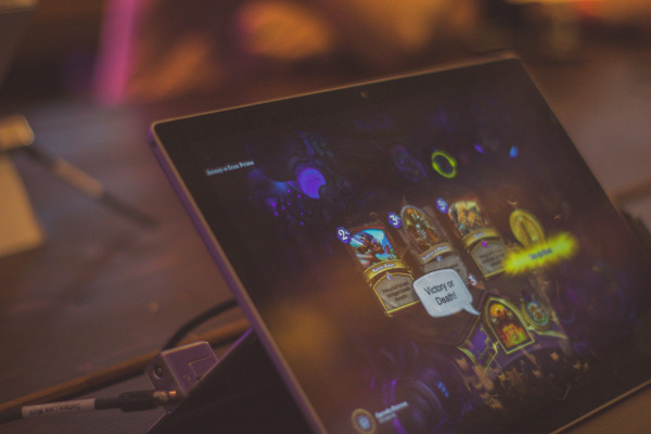 A handheld tablet with Hearthstone on the screen