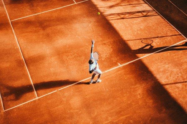 A tennis player throwing a ball in the air