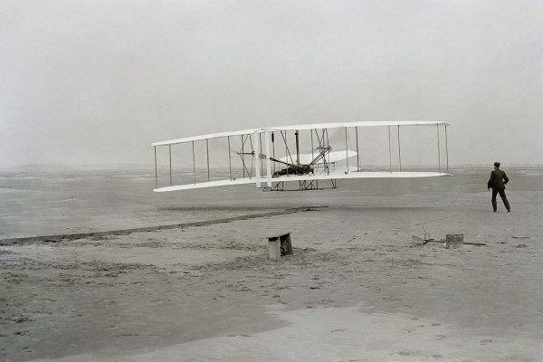 First successful flight of the Wright Flyer, by the Wright brothers. The machine traveled 120 ft (36.6 m) in 12 seconds at 10:35 a.m. at Kitty Hawk, North Carolina. Orville Wright was at the controls of the machine, lying prone on the lower wing with...