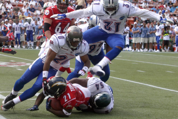 NFC defensive backs Ronde Barber and Roy Williams along with linebacker Jeremiah Trotter gang tackle AFC running back Ladainian Tomlinson during the 2006 Pro Bowl in Hawaii. More than 49,000 fans showed up to cheer on their favorite NFL players.