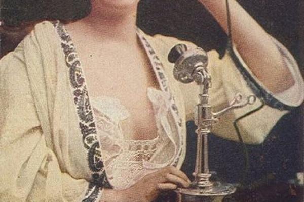 Woman using telephone, c. 1910.
