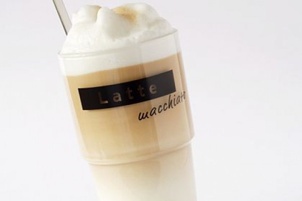 This photograph shows a glass of latte macchiato, which is a hot beverage made from steamed milk and espresso.