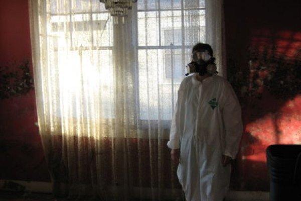 Man in hazard suit next to curtains