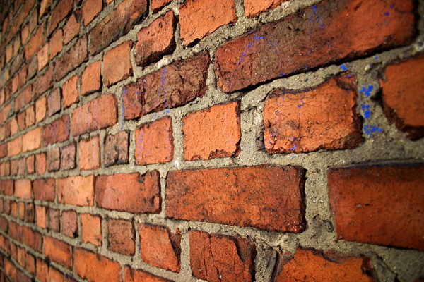 An old brick wall in English bond laid with alternating courses of headers and stretchers.