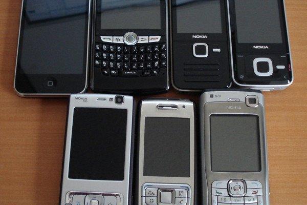 Assorted smartphones. From left to right, top row: iPhone 3G, Blackberry 8820, Nokia N78, Nokia N81, (bottom row) Nokia N95, Nokia E65, Nokia N70.