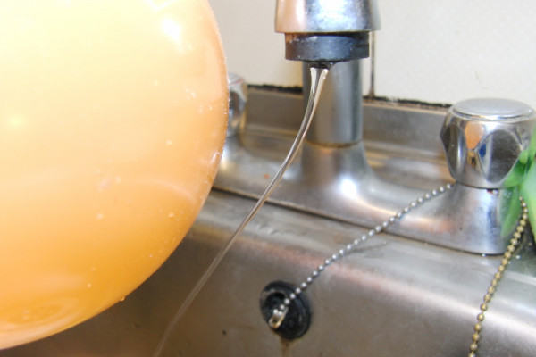 The charged balloon bends the stream of water