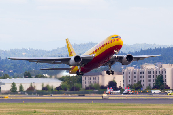 N785AX, a Boeing 767-200 in the DHL livery, operated by Airborne Express, departs runway 28R at Portland International Airport (KPDX).
