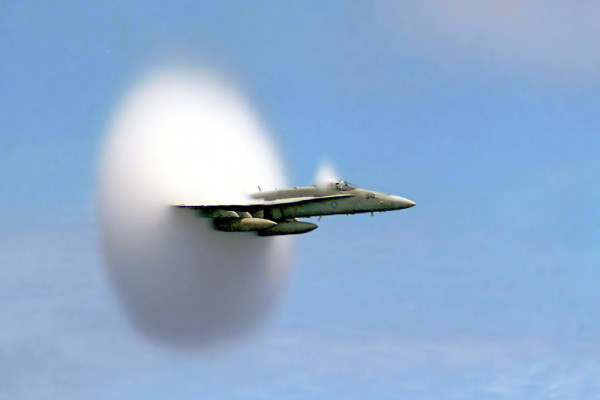 An F/A-18 Hornet breaks the sound barrier in the skies over the Pacific Ocean.