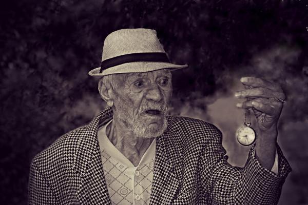 Elderly man holding a watch